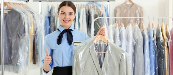 lady-gesturing-thumbs-up-while-holding-dry-cleaning