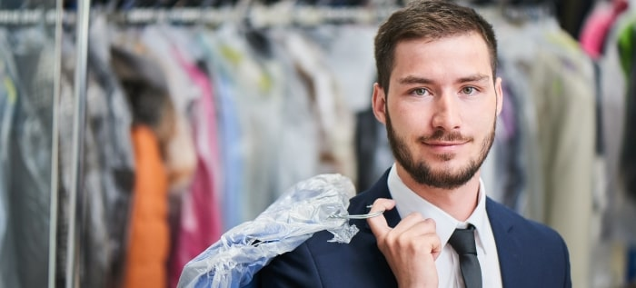 man smiles while holding dry cleaning